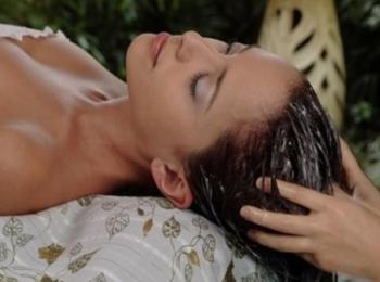 Девушке наносят укрепляющую маску с витаминами для волос