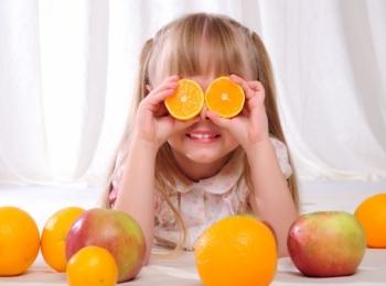 Девочка играет с половинками апельсина